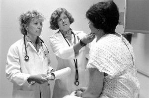 """""""Seattle physician with patient 1999"""" by Seattle Municipal Archives from Seattle, WA - Doctors with patient, 1999. Licensed under CC BY 2.0 via Wikimedia Commons"""